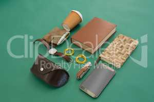 Disposable glass, wallet, organizer, wristwatch, pocketknife, mobile phone and sunglasses case on gr