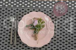 Fork and butter knife with flower and plate arranged on table cloth