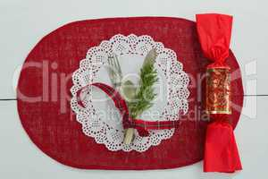 Cutlery with fern tied up with ribbon and chocolate on a placemat