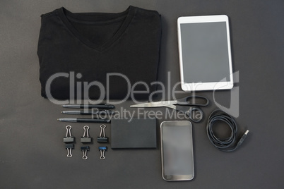 T-shirt, pen, wallet, scissors, usb cable, paper clip, mobile phone and digital tablet on black back