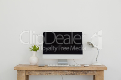 Vase, mobile phone, lamp and desktop pc on table