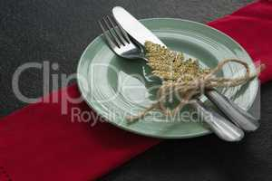 Christmas ornament, fork and knife in a plate with napkin