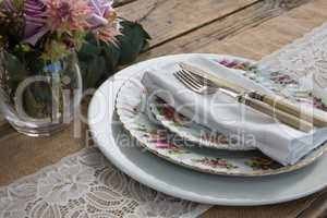 Plates with napkin, fork and butter knife arranged on wooden table