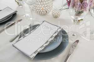 Menu card, plate and cutlery set elegantly on a table