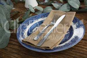 Plate with fork, butter knife and napkin on wooden table