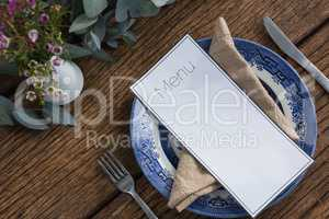 Plate with fork, butter knife, napkin and menu card on wooden table