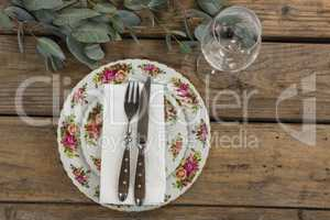 Floral pattern plate with cutlery set and wine glass