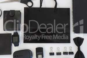 Electronic gadgets and black hued office accessories on white background