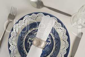 Fork, butter knife, spoon, napkin and lace placemat