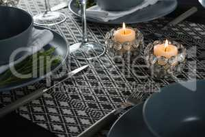 Elegance table setting with lit candle