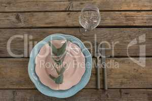 Leaf arranged on plates with empty wine glass and cutlery