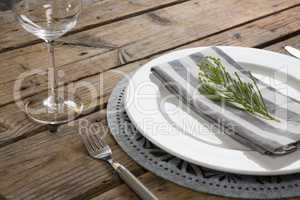 Fork, butter knife and wine glass with napkin and herb in a plate
