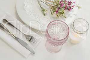 Flower kept over an embroidery napkin plate with cutlery