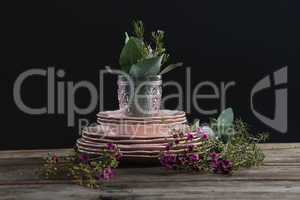 Crockery and floral decorations on wooden plank