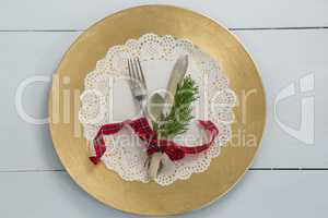 Cutlery with fern tied up with ribbon on a placemat