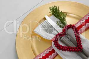 Cutlery with napkin and christmas decoration in a plate