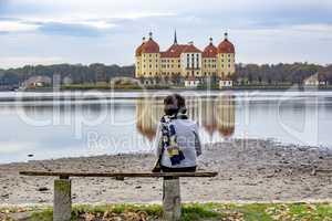 Person looks at the baroque castle Moritzburg