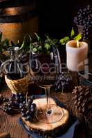 Red wine from a barrel with grapes and a glass of wine