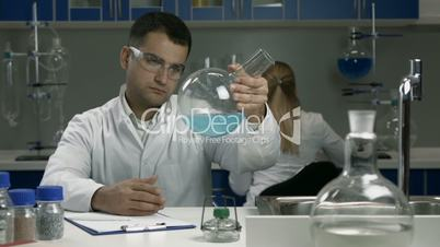 Male scientist examining flask with liquid in lab