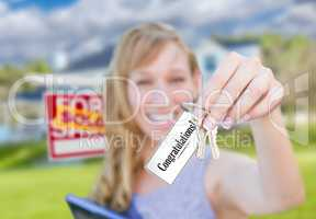 Woman Holding New House Keys with Congratulations Card In Front