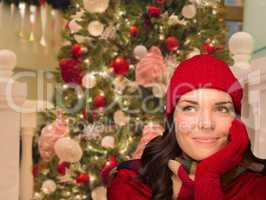 Warmly Dressed Female In Front of Decorated Christmas Tree.