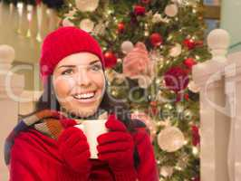 Warmly Dressed Female With Mug In Front of Decorated Christmas T