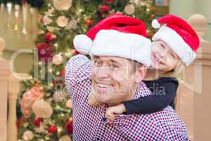 Father and Daughter Wearing Santa Hats In Front of Decorated Chr