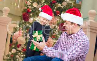 Happy Young Girl and Father Wearing Santa Hats Opening Gift Box