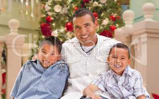 Hispanic Young Father and Sons In Front of Decorated Christmas T