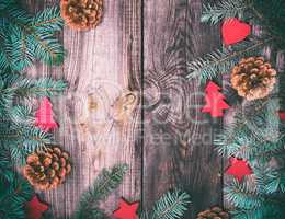 gray wood background with green spruce branches and Christmas de