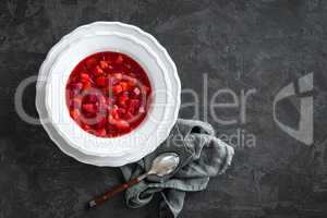 Vegetarian hot diet beetroot soup with vegetables on plate, top view, dark background