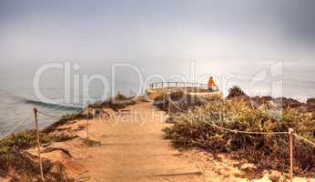 Lone man stands at a vista as Fog drifts in over the ocean at Cr