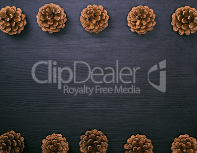 brown pine cones on a black wooden background