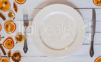 white empty dining plate with cutlery on a white wooden surface