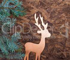 A wooden background with a green spruce branch and a wooden toy