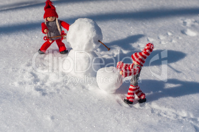 Two small wooden man in the scene of building a snowman among th
