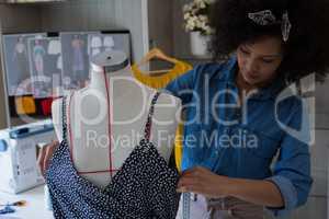 Fashion designer designing a dress on mannequin