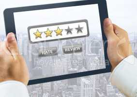 Hand holding tablet over city with star ratings and review button