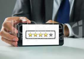 Hand holding phone with star ratings review