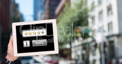 Hand holding tablet with Rate button and star ratings review icons in city