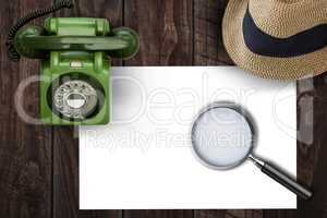 Magnifying glass on paper on side of brown hat and green phone
