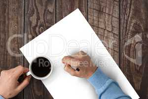 Man writing on paper while drinking coffee