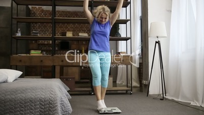 Charming woman with scale celebrating weight loss
