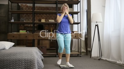 Upset woman is unhappy with weight gain indoors