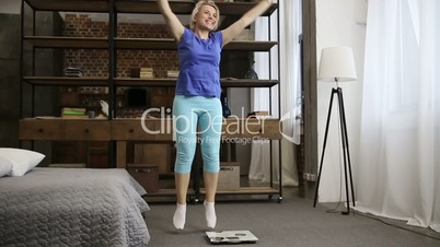 Lovely fit woman celebrating weight loss indoors