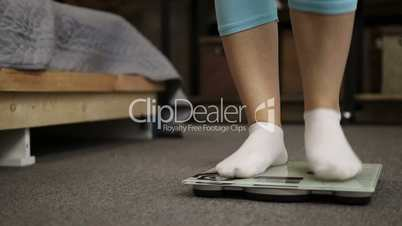 Female feet in socks standing on weight scale