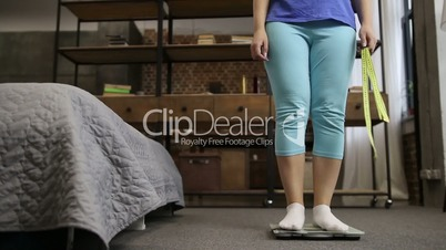 Charming woman standing on scale measuring weight