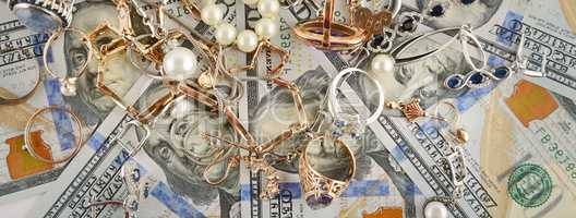Background of American dollars and jewelry. Flat lay, top view.