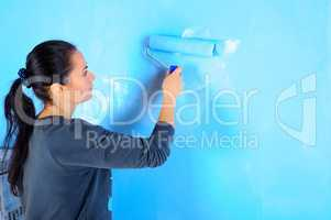 girl painter engaged in painting the walls