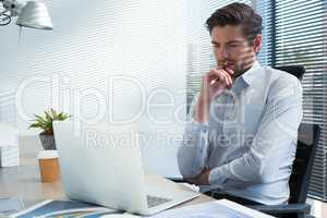 Thoughtful male executive looking at laptop